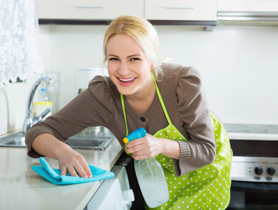 Housewife cleaning furniture in kitchen